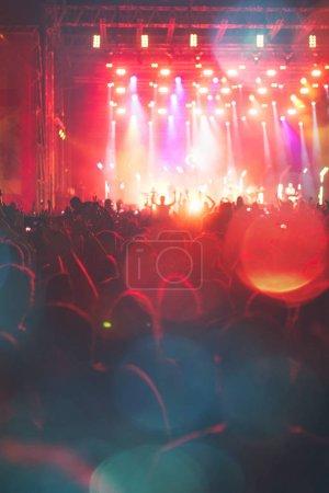 Photo pour Silhouettes de concert festival se pressent devant les lumières de la scène lumineuse. Les gens méconnaissables et effets colorés - image libre de droit