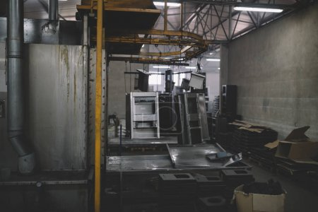 Metallurgy industry. Interior details from factory for production of heavy pellet stoves and boilers. Extremely dark conditions and visible noise. Focus on foreground