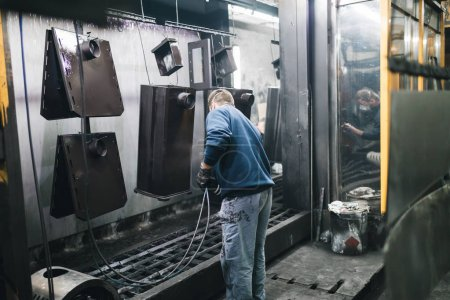 Metallurgy industry. Factory for production of heavy pellet stoves and boilers. Manual worker painter on his job. Extremely dark conditions and visible noise