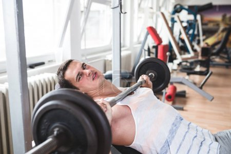 Young attractive adult man exercising and doing weight lifting at fitness gym. Sport training indoors