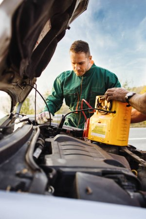 Photo for Two road assistant workers in towing service trying to start car engine with jump starter and energy station with air compressor. Roadside assistance concept. - Royalty Free Image