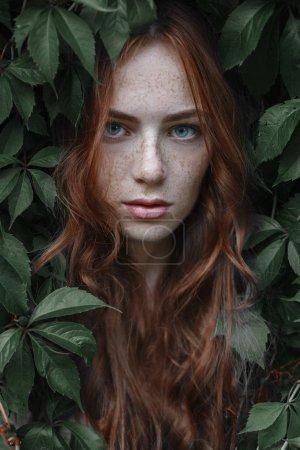 Photo pour Belle rousse jeune dans les feuilles vertes - image libre de droit