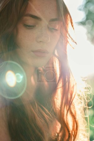 Photo for Beautiful redhead girl in sun rays in summer - Royalty Free Image