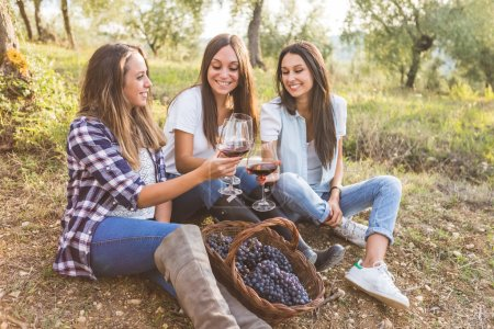 Women toasting with wine in the garden