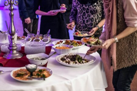 Photo for People group catering buffet at a food table luxury restaurant with meat, bread and different salad - Royalty Free Image