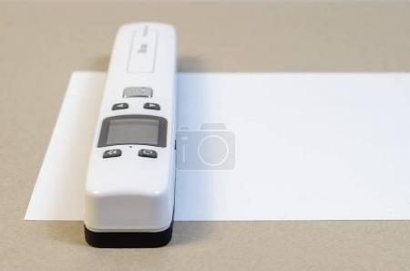 A small handheld white scanner scans the document on the table. Portable scan paper. Scanning.