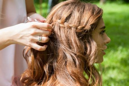 Hairstylist braiding pigtails to young girl outdoor. Creating braids.