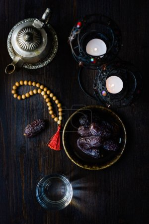 Top view of water for iftar, islamic rosary and ramadan dates