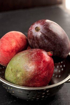 Fresh and ripe mango on metal colander