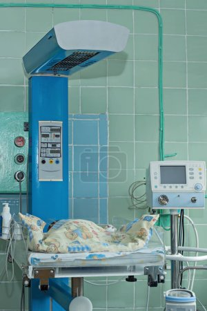 Newborn baby on infant warmer in neonatal intensive care unit