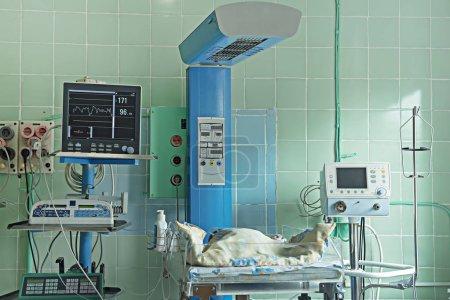 Newborn baby sleeping and equipment in neonatal intensive care unit