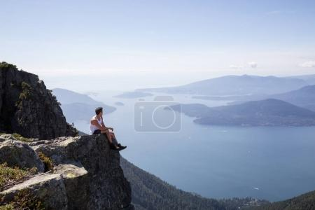 Fit Latin American Male Hiker is sitting on top of the rocky peak overlooking the beautiful landscape. Picture taken on the way up to The Lions Mountain, North of Vancouver, British Columbia, Canada.