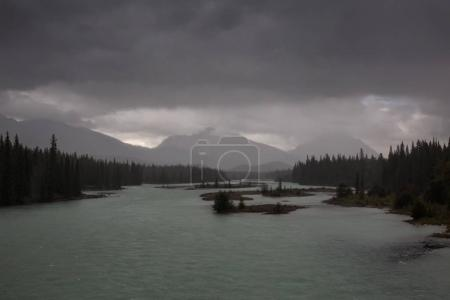 Dark rainy clouds over Athabasca River on Icefields Pkwy in Jasper National Park, Alberta, Canada.