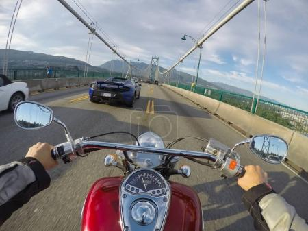 Riding a cruiser motorcycle on Lions Gate Bridge towards North Vancouver, British Columbia, Canada. Taken during a sunny summer day.