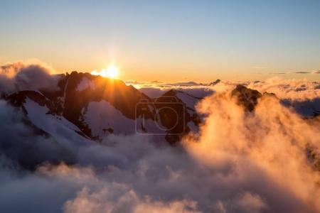 Beautiful aerial landscape view of Mountain Peaks near Squamish, North of Vancouver, British Columbia, Canada. Taken during a colorful summer sunset.
