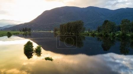 Reflection of the mountains on a river during a cloudy golden sunset. Taken in Nicomen Slought in Fraser Valley, British Columbia, Canada.