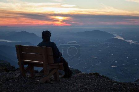 Adventurous man on top of the mountain
