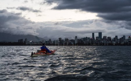 Adventurous girl is kayaking during a dramatic sunrise with city skyline in the background. Taken in Vancouver, British Columbia, Canada.