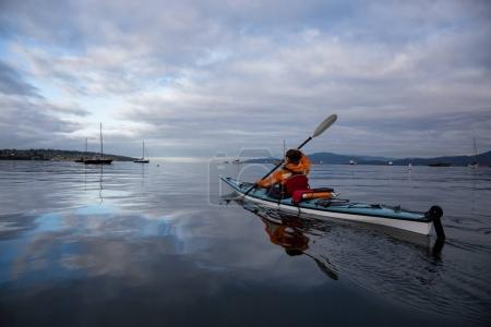 Woman kayaking in the ocean during a vibrant and cloudy morning. Taken near Kitsilano in Vancouver City, British Columbia, Canada. Concept of Adventure, Recreation and Fitness