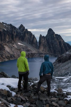 Adventurous friends are enjoying the beautiful and rugged mountain landscape during a cloudy sunrise. Taken in Silver Lake, far remote East of Vancouver and Seattle, Washington State, America.