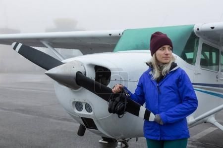 Young Caucasian Female Student Pilot is standing in front of a Single Engine Airplane at the Airport. Taken during a foggy winter morning in Pitt Meadows, Vancouver, BC, Canada.