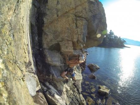 Man Rock Climbing a steep rockface during a bright summer day. Taken in Copper Cover, Horseshoe Bay, West Vancouver, British Columbia, Canada.