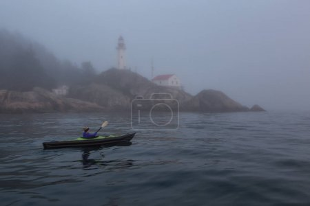 Adventurous woman is sea kayaking near a lighthouse during a vibrant and foggy winter sunset. Taken in Horseshoe Bay, West Vancouver, BC, Canada. Concept: adventure, holiday, vacation, explore