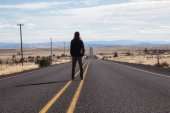 Man is standing in the middle of the long road during a vibrant sunny day. Taken in Oregon, North America.