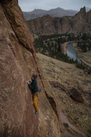 Photo pour L'homme aventureux fait de l'escalade sur le flanc d'une falaise escarpée lors d'une soirée d'hiver nuageuse. Prise à Smith Rock, Oregon, Amérique du Nord . - image libre de droit