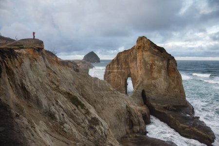 View of Cape Kiwanda with a man taking pictures on top of the cliff of stormy ocean. Taken in Pacific City, Oregon Coast, United States of America.