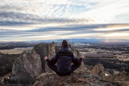 Photo for Adventurous man sitting in a meditation pose on top of a cliff during a vibrant sunset. Taken in Smith Rock, Oregon, America. Concept: adventure, freedom, travel, holiday, vacation - Royalty Free Image