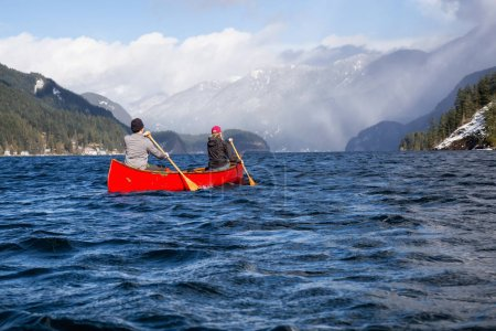 Photo for Couple friends on a wooden canoe are paddling in an inlet surrounded by Canadian mountains. Taken in Indian Arm, near Deep Cove, North Vancouver, British Columbia, Canada. - Royalty Free Image