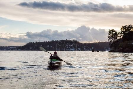 Adventurous girl is kayaking on an inflatable kayak during a vibrant winter sunset. Taken in Indian Arm, Deep Cove, Vancouver, BC, Canada. Concept: Adventure, Holiday