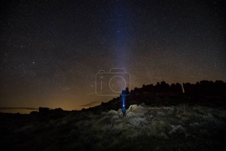 Night scene of a rugged mountain landscape with the sky full of stars and a man standing with headlamp. Taken in Frenchman Coulee, Vantage, Washington, USA.