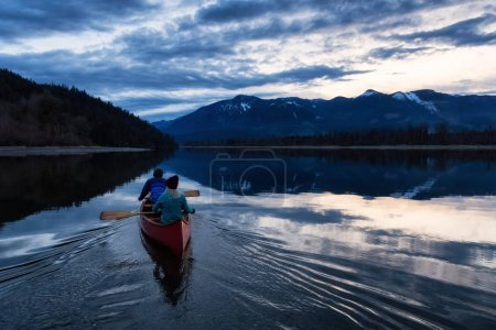 Photo for Adventurous people on a wooden canoe are enjoying the beautiful Canadian Mountain Landscape during a vibrant sunset. Taken in Harrison River, East of Vancouver, British Columbia, Canada. - Royalty Free Image
