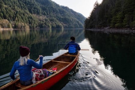 Couple friends canoeing on a wooden canoe during a sunny day. Taken in Harrison River, East of Vancouver, British Columbia, Canada.