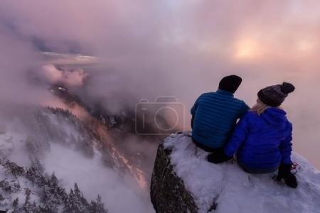Young couple sitting on the side of a steep cliff overlooking the beautiful view during a vibrant sunset. Taken on top of St Mark's Peak, North of Vancouver, BC, Canada.