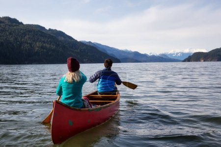 Couple friends canoeing on a wooden canoe during a sunny day. Taken in Harrison Lake, East of Vancouver, British Columbia, Canada.