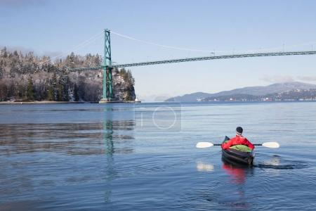 Adventurous man kayaking on an inflatable kayak near Lions Gate Bridge. Taken in North Vancouver, British Columbia, Canada.
