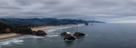 Photo for Cannon Beach, Oregon, United States. Beautiful Aerial Panoramic View of the Rocky Pacific Ocean Coast during a cloudy summer sunrise. - Royalty Free Image