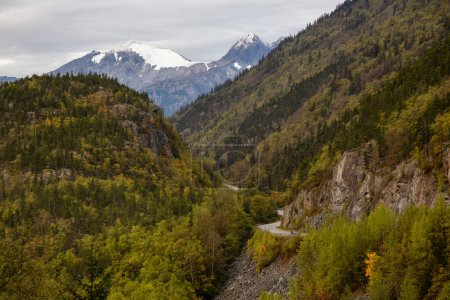 Photo for Scenic Road in the valley surrounded by the beautiful Mountain Landscape during a cloudy summer morning. Taken near Stagway, Alaska, United States of America. - Royalty Free Image