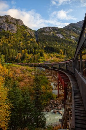 Photo for Skagway, Alaska, United States - September 24, 2019: Old Historic Railroad Train is going over a wooden bridge up White Pass with tourists during a cloudy summer morning. - Royalty Free Image