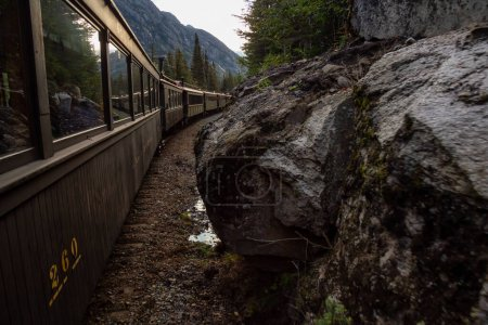 Photo for Skagway, Alaska, United States - September 24, 2019: Old Historic Railroad Train is going up White Pass with tourists during a cloudy summer morning. - Royalty Free Image