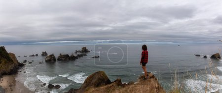Photo for Ecola State Park, Cannon Beach, Oregon, United States. Adventurous Girl standing at the Rocky Cliff on Pacific Ocean Coast during a cloudy summer sunrise. - Royalty Free Image