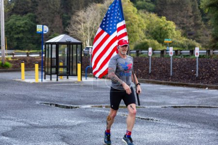 Photo for Neskowin, Oregon, United States - September 8, 2019: Proud member of Team RWB is running outside with an American Flag during a summer morning. - Royalty Free Image