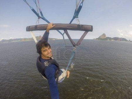 Brazil, Rio de Janeiro - March 07, 2018: Man taking selfie while parasailing in Guanabara Bay