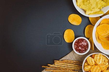 Kartoffelchips und Snacks auf schwarzem Schiefertisch, Draufsicht