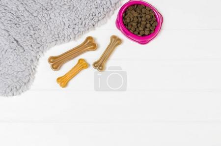 Dry dog pet food on white wooden background top view