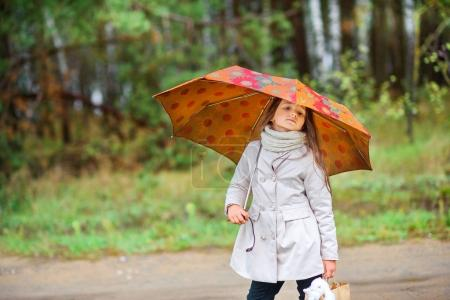 girl is walking under an umbrella