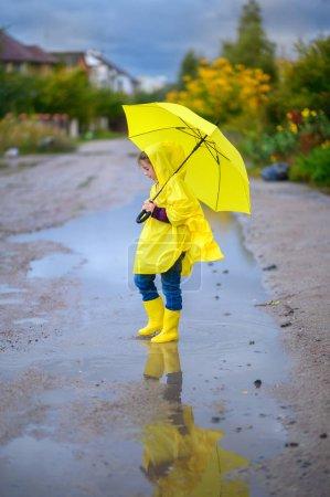 Nettes kleines Mädchen im Regenmantel und mit einem gelben Regenschirm in der Hand geht durch Pfützen, geht in Stiefeln und spritzt